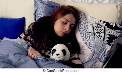 Ill young woman sleeping in bed with panda toy