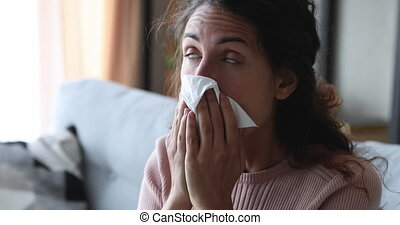 Unhealthy ill young woman holding tissue suffering from allergy, sniffles, stuffy nose problem. Sick allergic lady having virus infection disease symptoms, blowing running nose at home. Close up view