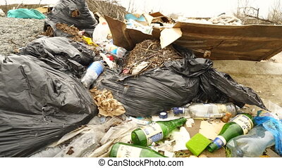 Illegal dumping site with household garbage and construction...