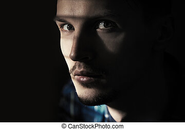 Illegal man in the dark prison. Close-up portrait