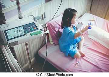 Illness asian child admitted with saline iv drip on hand.