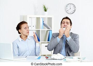 Illness - Image of businessman sneezing while his partner...