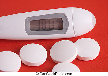 Illness - Krankheit - Thermometer with some pills on red...