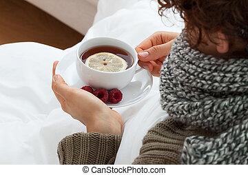 Sick woman drinking hot tea with lemon and raspberries