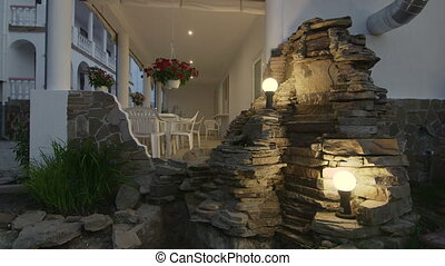 Illuminated back garden of two storey house with white...