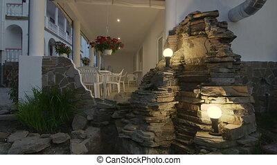 Illuminated back garden of two storey house with white...