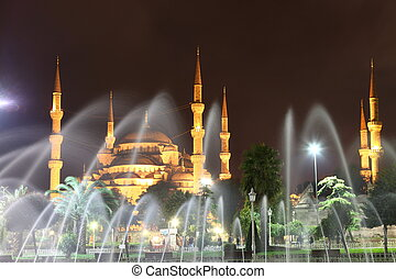 Illuminated Blue Mosque in Istanbul behind fountain at night