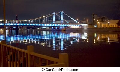 Illuminated bridge over the river in the city at night