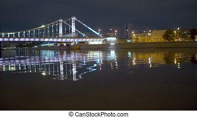 Illuminated bridge over the river in the city at night. Panoramic view of night city quay
