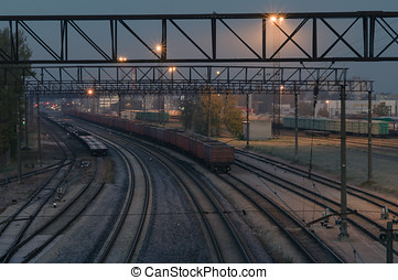 Illuminated cargo train station by night. Curve platform with containers