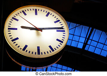 illuminated clock in front of railway station roof