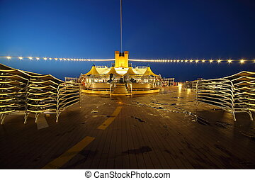 illuminated deck of cruise ship at evening. bar and tables in center of image.