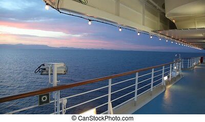 illuminated deck of cruise ship moving in evening sea