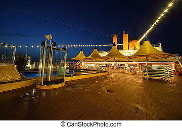 illuminated deck of ship at evening. bar and tables in center of image.