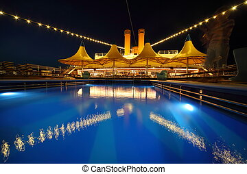 illuminated deck of ship at evening. swimming pool in deck of ship