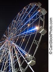 Illuminated ferris wheel at night. City intertainment.