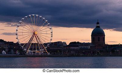 Illuminated ferris wheel in Toulouse at dusk
