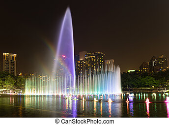 Illuminated fountain at night in modern city