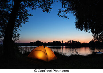 Illuminated from inside orange tent on the shore of lake among silhouettes of trees