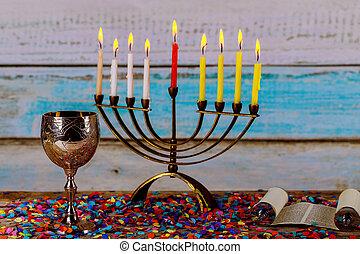 Illuminated Hanukkah menorah candles on gold menorah