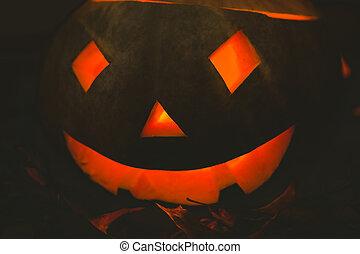Illuminated jack o lantern in darkroom during Halloween - ...