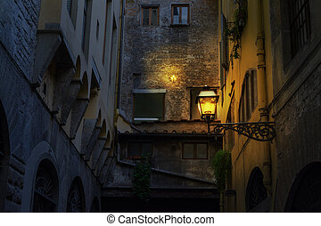 Illuminated lamp in a rustic corner in Florence at night