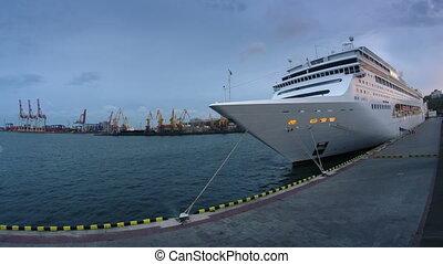 Illuminated luxury cruise liner leaves port at night timelapse