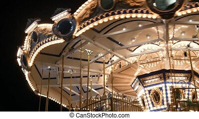 Illuminated merry go round in park. Brightly illuminated roundabout spinning in wonderful amusement park at night