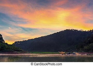 Illuminated orange sunset sky and tranquil lake water surface