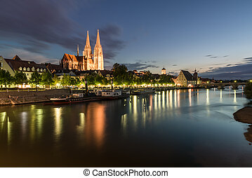 Illuminated promenade in Regensburg with view to the Cathedral and stone bridge, Germany