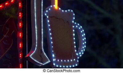 Illuminated pub bar neon sign beer tankard with head of foam on night city street.
