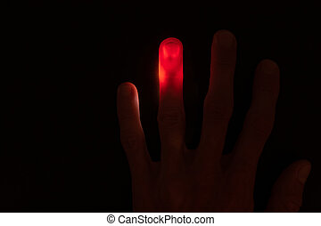 Illuminated red finger on black background - Abstract ...