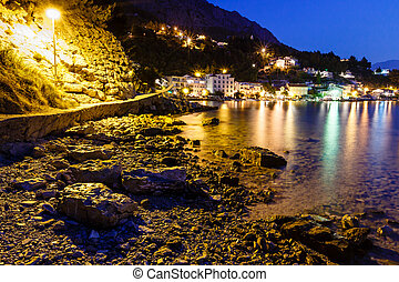 Illuminated Rocky Beach and Transparent Mediterranean Sea in the Night, Croatia