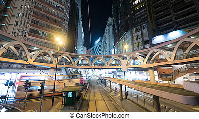 Illuminated street of Hong Kong with rails and pedestrian...