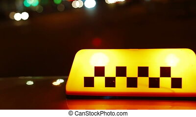 Illuminated taxi sign at night in the city