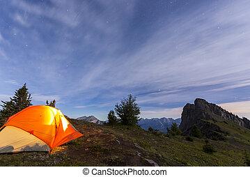 Illuminated tent camping on ridgeline of mountain