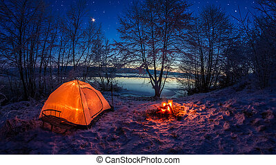 Illuminated tent in the winter camp by the lake at night with stars