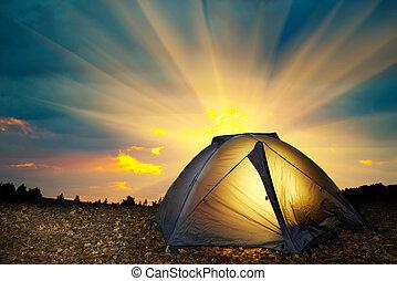 Illuminated yellow camping tent under stars at night....