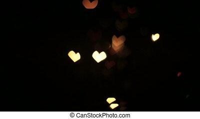 Illumination garland decoration blinking on heart shaped bokeh background.