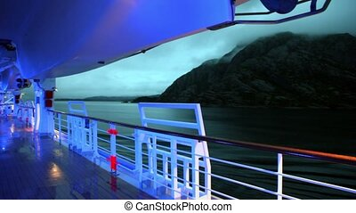 Illumination on deck of ship which floats near coastline