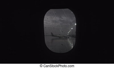 Illuminator with rain streaks, view to airport from moving plane