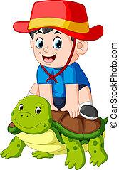 a boy is sitting on a big turtle