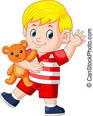 a cute boy play with the orange teddy bear