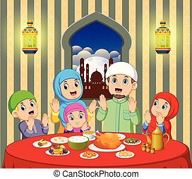A happy family are praying before eating in their house with beautiful view from the window