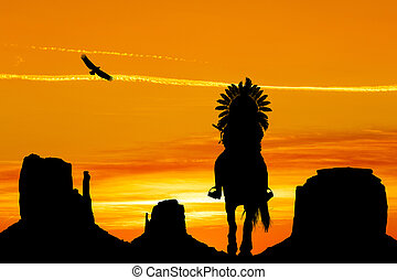 American Indian on horseback in monument Valley at sunset