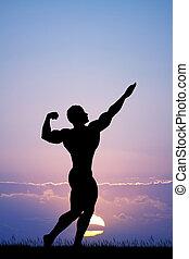 bodybuilder silhouette at sunset - illustration of...