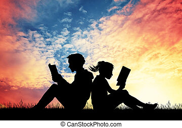 couple reading a book at sunset