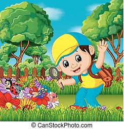 Cute boy holding magnifying glass in a flower garden