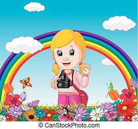Cute girl in a flower garden with rainbow