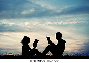 man and woman reading a book at sunset